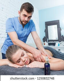 Portrait of young woman enjoying relaxing massage by professional masseur