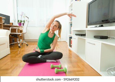 Portrait of a young woman exercising at home. She is sitting cross-legged on the floor and doing stretching exercise with her arms above her head.