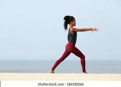 Portrait of a young woman exercising with yoga stretches at the beach