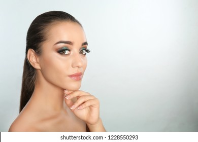 Portrait of young woman with eyelash extensions and beautiful makeup on light background. Space for text