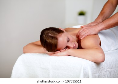 Portrait of a young woman with eyes closed receiving a massage at a spa day