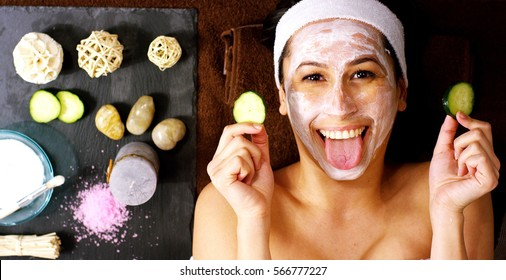 Portrait of young woman with facial mask and cucumber treatment on her face have a relax in a wellness center. Concept of skincare, cosmetics, beauty salon, facial treatment, facial massage, wellbeing