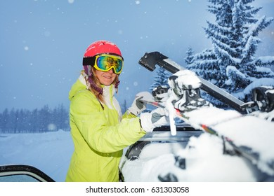 Portrait of young woman fastening skis on car roof