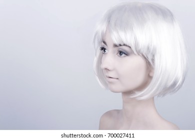 Portrait of young woman / female / girl with white care wig / hair and bare shoulders posing