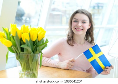 Portrait young woman with the flag of Sweden. A  female student in a bright room near a bouquet of yellow tulips.