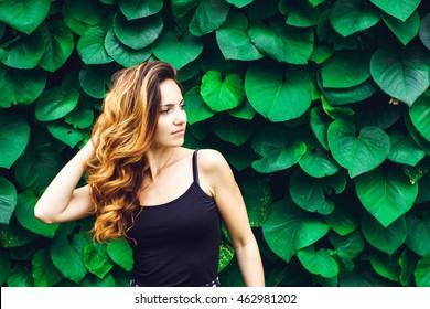 Retrato de mulher jovem com as sardas e cabelos encaracolados, contra o fundo do parque verde verão, folhas verdes. Beleza natural.