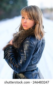 Portrait of young woman in freezing winter weather standing outdoors