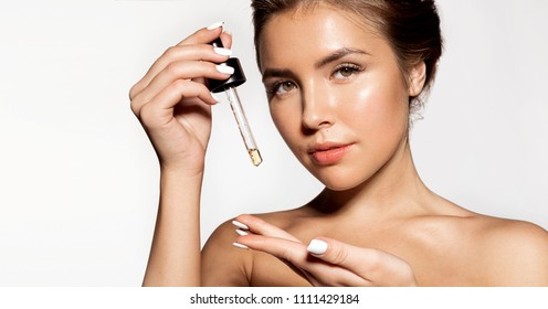 Portrait of  young woman with fresh perfect skin posing at studio. Glorious girl applying liquid oil for skincare. Cosmetology and treatment concept. Isolated on grey background