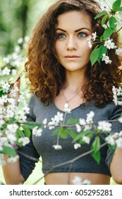 Portrait of young woman in  garden in the spring time. Almond flowers blossoms.