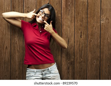 portrait of young woman gesturing happy against a wooden wall