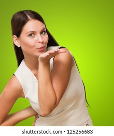 Portrait Of A Young Woman Giving Flying Kiss against a green background