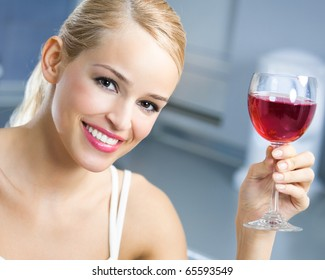 Portrait of young woman with glass of red wine, indoors