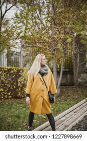 Portrait of a young woman in glasses with long blond hair in a yellow coat in an autumn park