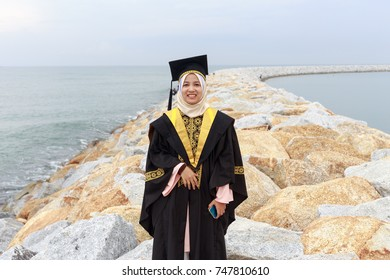 3feeb61fc39 Portrait of young woman in graduation dress smiling and standing on rocks  of beach side.