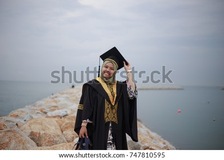 d1feeac6e9 Portrait of young woman in graduation dress smiling and standing on rocks  of beach side.