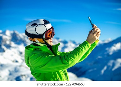 Portrait of young woman in green jacket and helmet taking a selfie on sunny day in French Alps, Tignes.