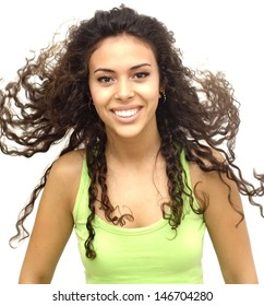 Portrait of a young  woman with green shirt and her hair in the wind over white background