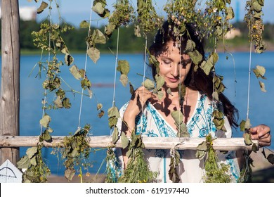 Portrait of a young woman harvesting herbs in crops for drying them in the sun. Traditional Midsummer Eve festival celebration in Sweden, Finland concept.