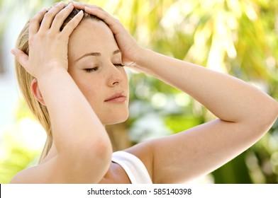 Portrait of a young woman has a headache, migraine, closeup