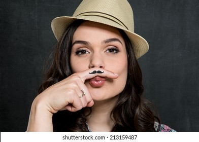 Portrait Of Young Woman In Hat With Painted Mustache Over Gray Background