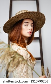 portrait of young woman in hat and vintage style dress posing