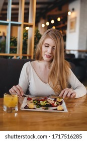 Portrait of a young woman having a breakfast in a cafe