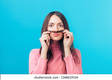 Portrait of young woman having fun shows moustache hair isolated on blue background. Humor concept
