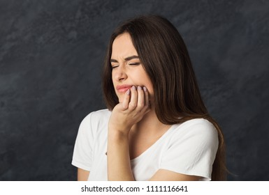 Portrait of young woman having toothache. Attractive girl with pain grimace at dark studio background. Health care and dental issues concept, copy space