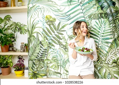 Portrait of a young woman with healthy food on the beautiful wall with green plants drawings on the background
