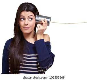 portrait of a young woman hearing through a tin can over a white background