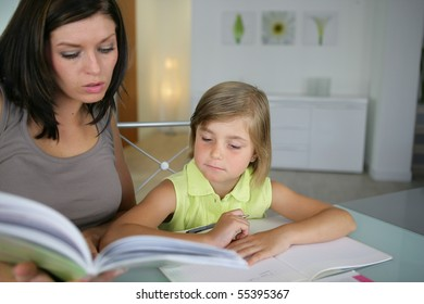 Portrait of a young woman helping a little girl in doing her homework