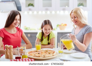 Portrait of young woman and her daughters sitting by dinner table and having meals