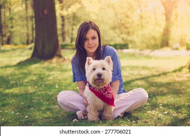 Portrait of a young woman with her dog in the park on a sunny day