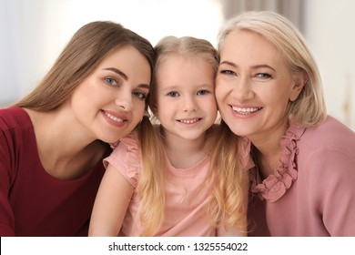 Portrait of young woman, her mature mother and daughter indoors