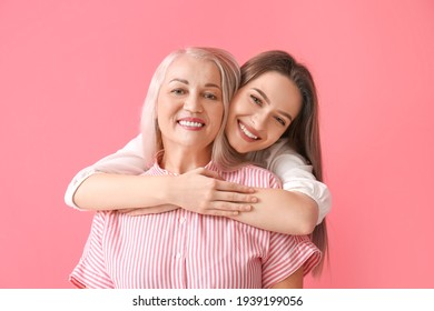 Portrait of young woman and her mother on color background