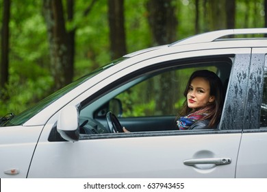Portrait of a young woman with her new car