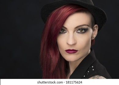 Portrait of a young woman in her thirty's, with Red hair, wearing a black hat. She has bright brown eyes, and a piercing in her left ear.