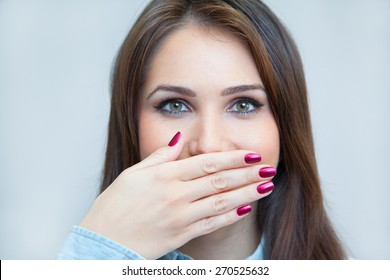 portrait of a young woman hiding her mouth with a hand