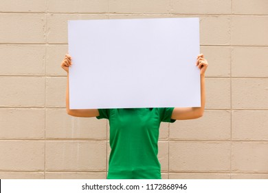 Portrait of young woman holding blank white board on brick wall background.