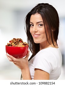portrait of a young woman holding a bowl of cereals indoor