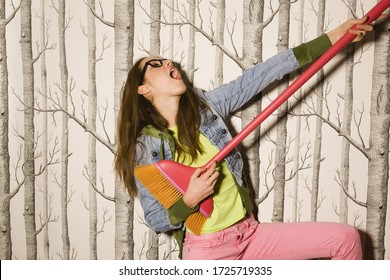 Portrait of young woman holding broom and singing