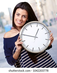 portrait of young woman holding clock at street
