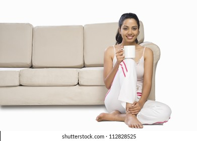 Portrait of a young woman holding a coffee mug