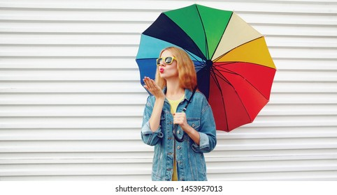 Portrait young woman holding colorful umbrella blowing red lips sending sweet air kiss on white wall background in city