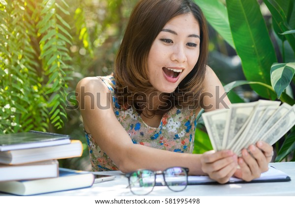 portrait of young woman holding and counts money dollar bills in hands, lending and banking services or financial reward savings.