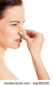 Portrait of a young woman holding her nose because of a bad smell. Isolated on white.