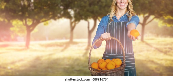Portrait of young woman holding oranges in wicker basket against trees growing in field