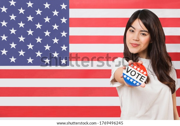Portrait of young woman holding out vote badge against American flag