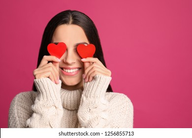 Portrait of young woman holding paper hearts near eyes on color background. Space for text