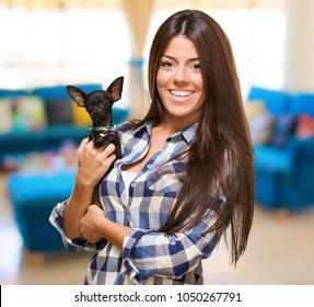 Portrait Of A Young Woman Holding Puppy at her home